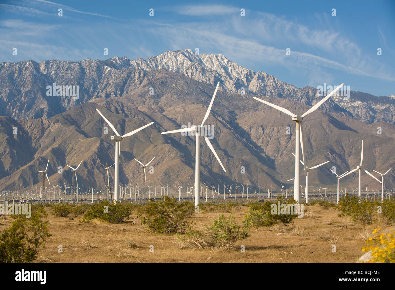 Energy generating windmills in desert with snow capped San Jacinto Mountains in background Palm Springs California - Stock Image