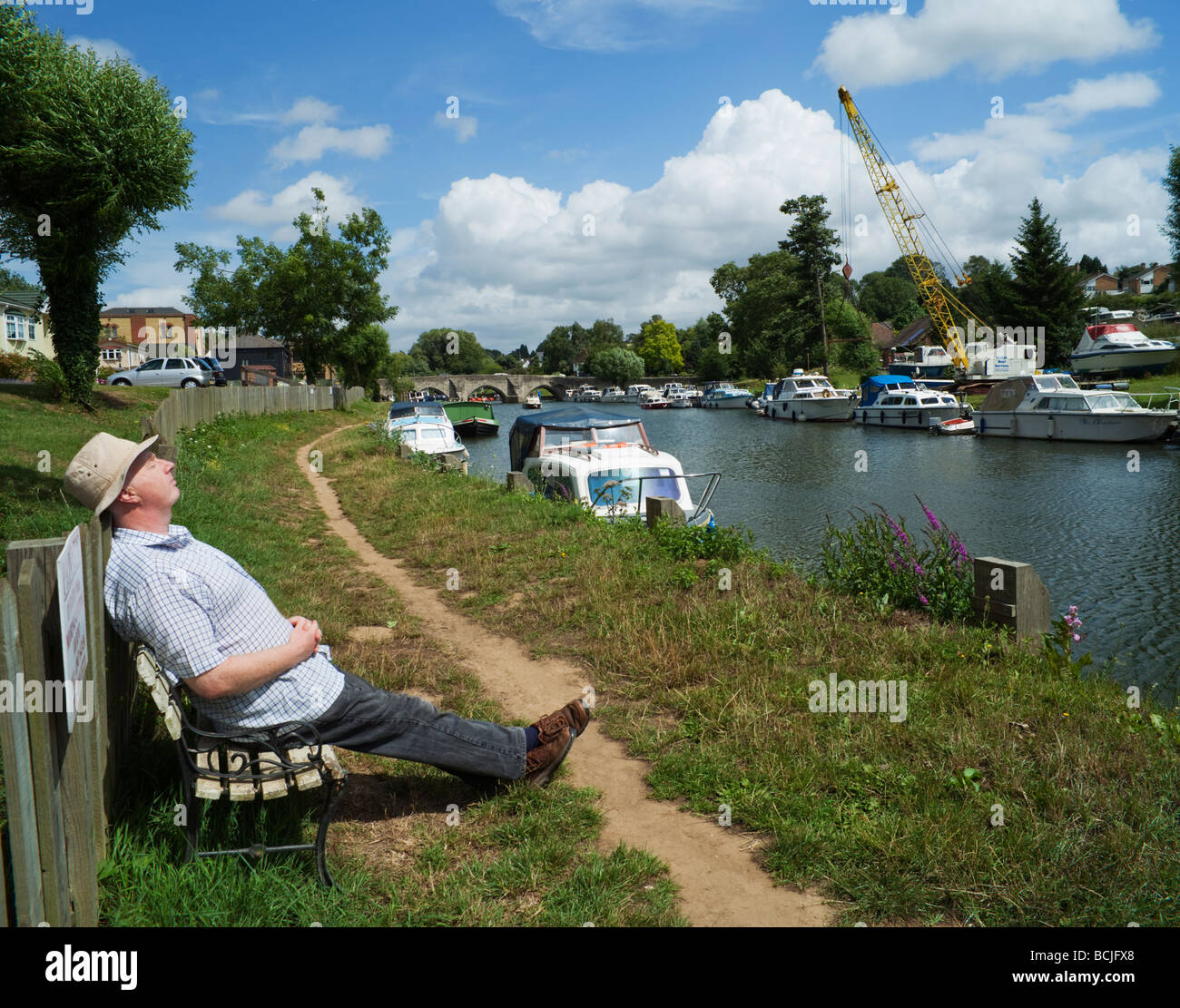 Man resting on a bench. Medway River East Farleigh Kent England UK - Stock Image