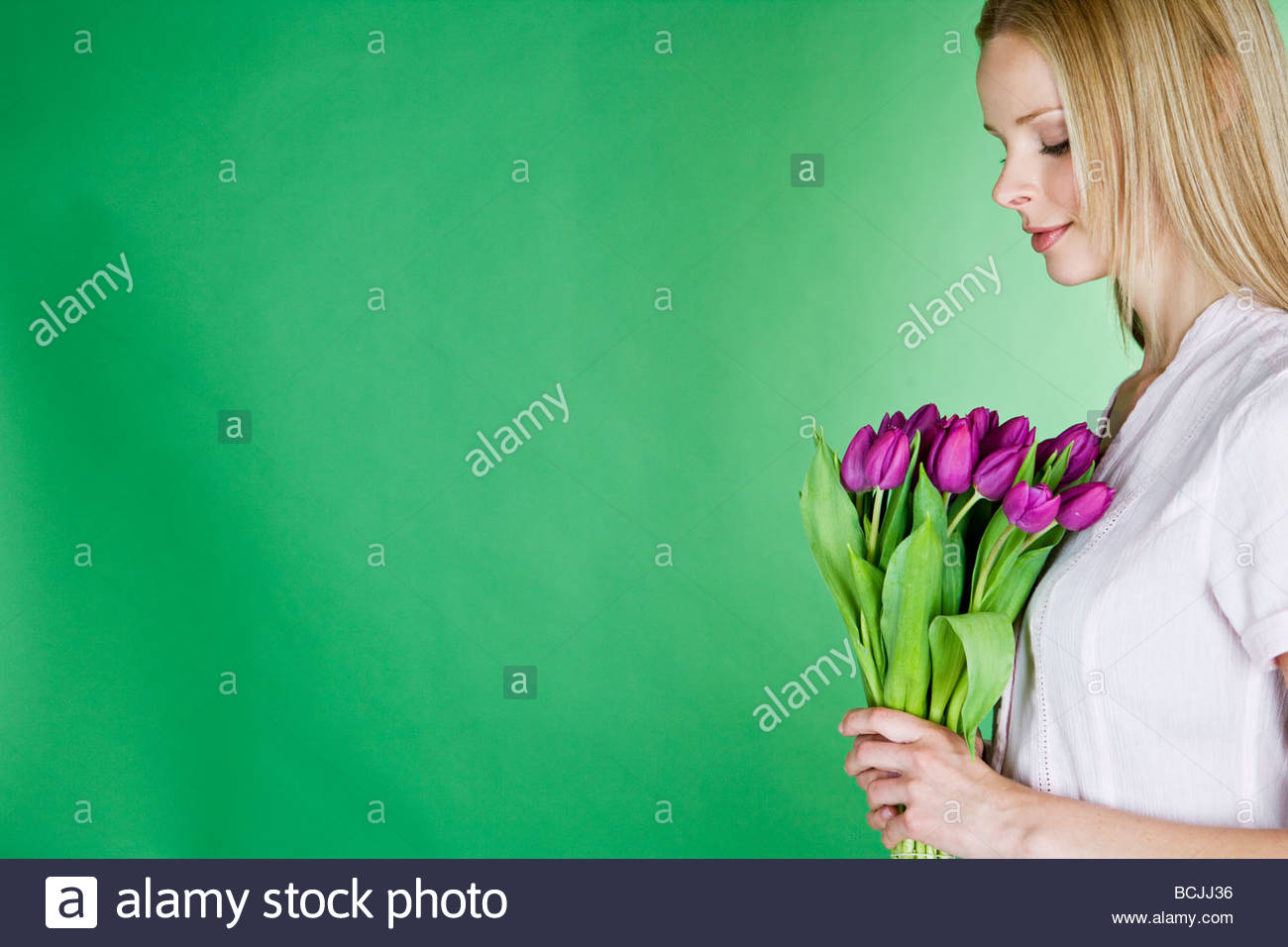 A young blonde woman holding a bunch of purple tulips, in profile - Stock Image