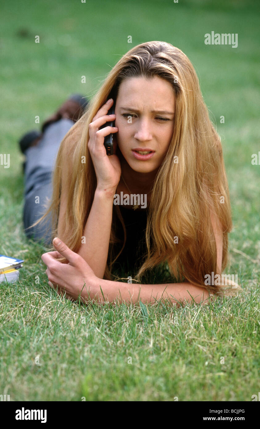 1990s: Annoyed teenage girl on meadow field, listening annoyed to her 1990's Nokia cellphone. - Stock Image