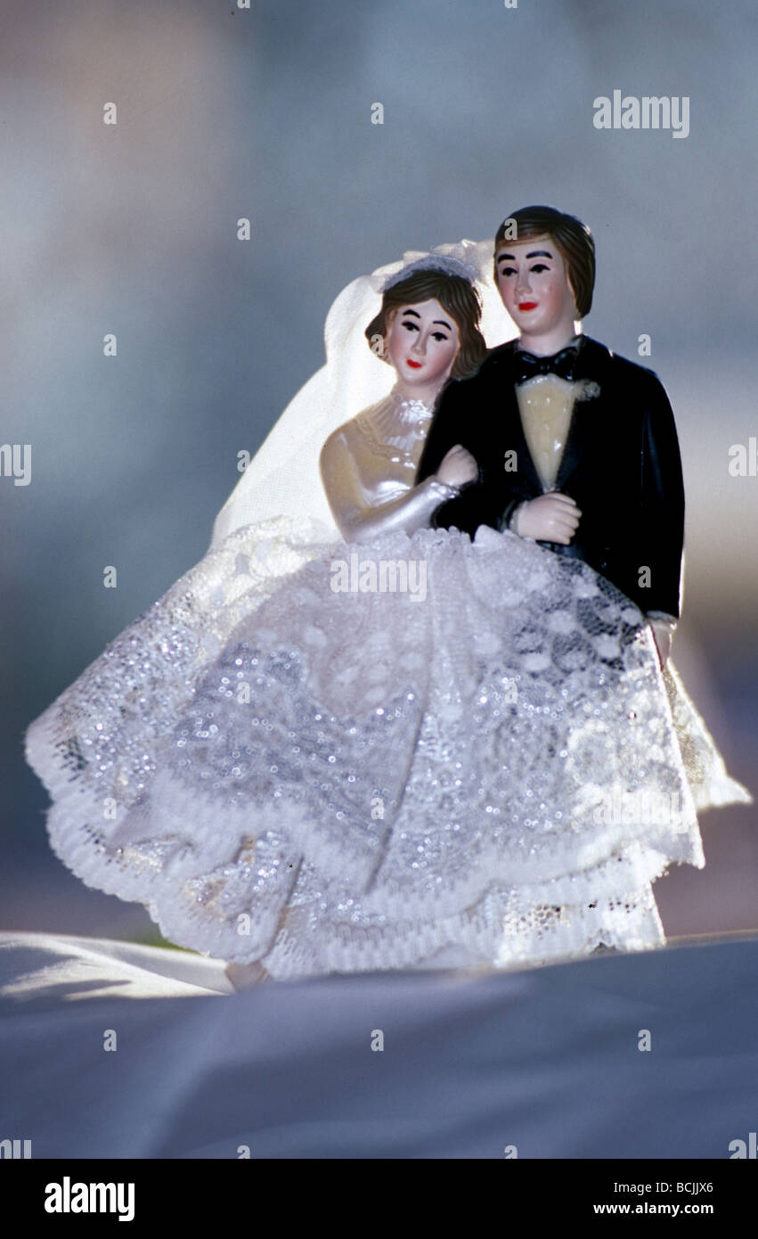 Metaphor for happy marriage : Cake toppers bride and groom figurines standing close, she is holding him. - Stock Image