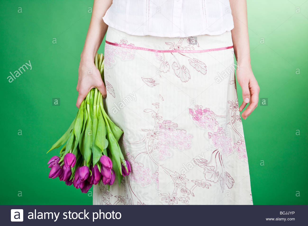 A woman holding a bunch of purple tulips - Stock Image