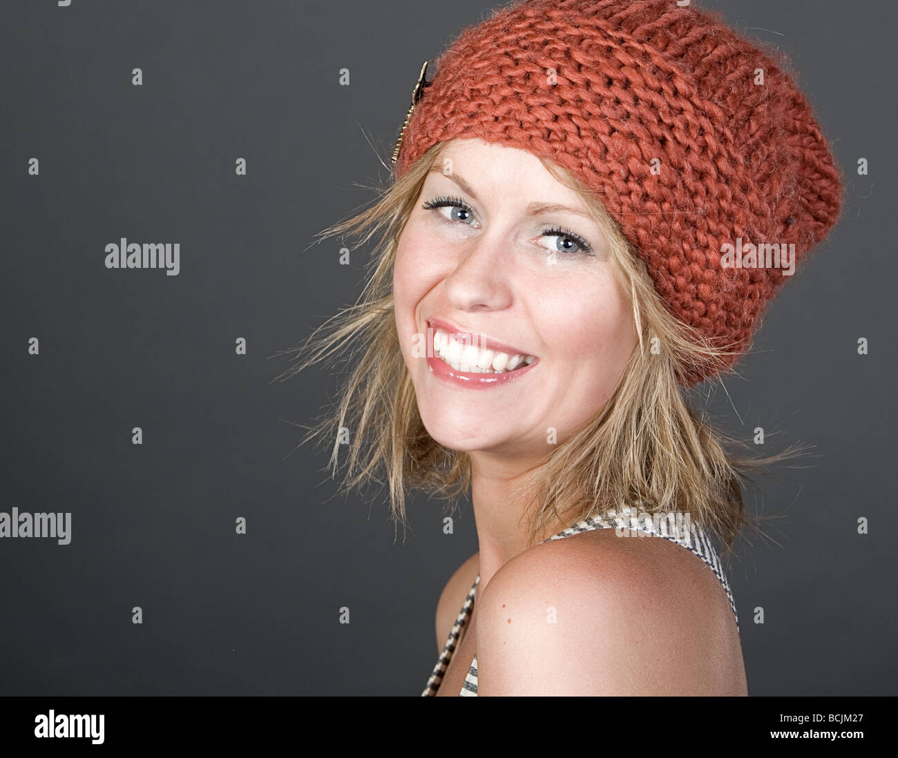 Shot of an Attractive Blonde Girl Smiling in Orange Beanie Hat Stock Photo