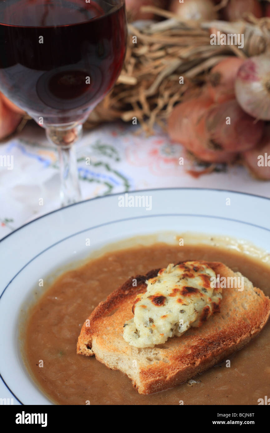 A bowl of French onion soup with fromage en crout cheese with garlic and herbs on toast croutons and a glass of - Stock Image