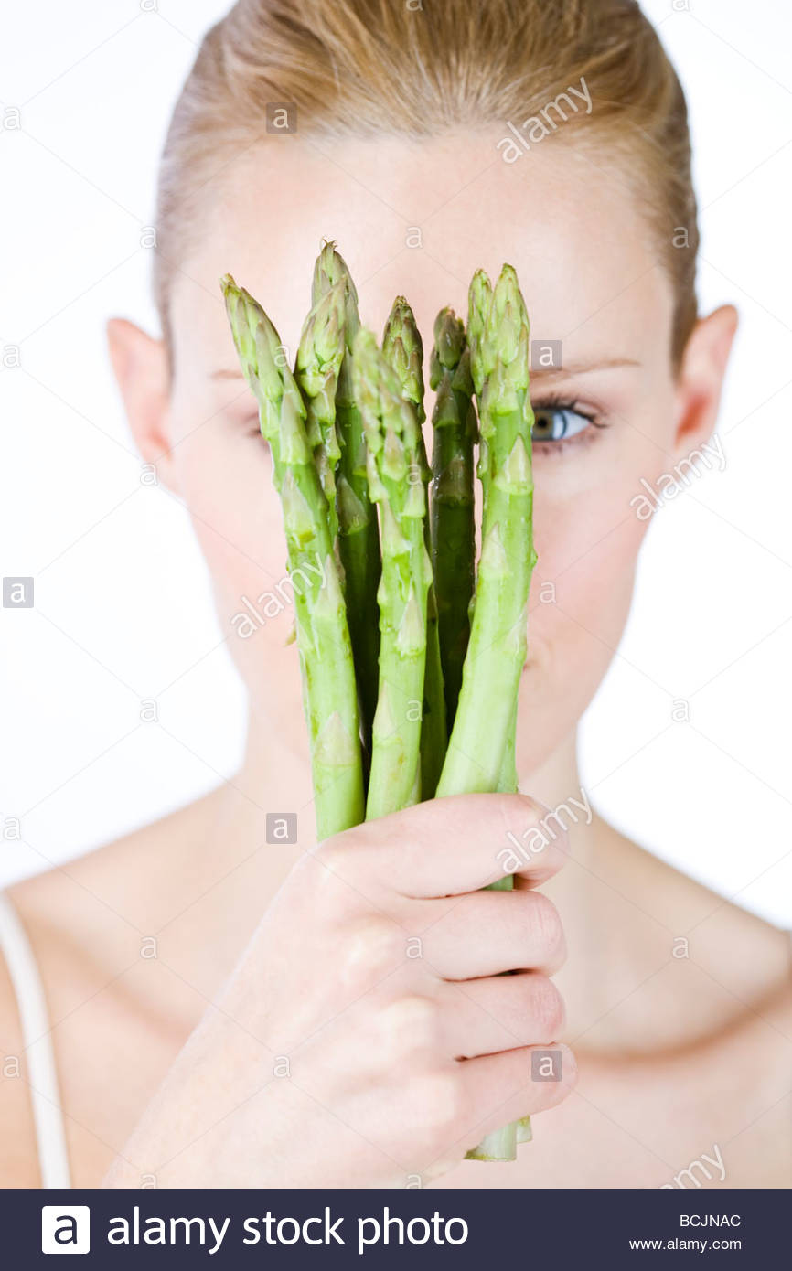 A young blonde woman holding asparagus in her hands - Stock Image