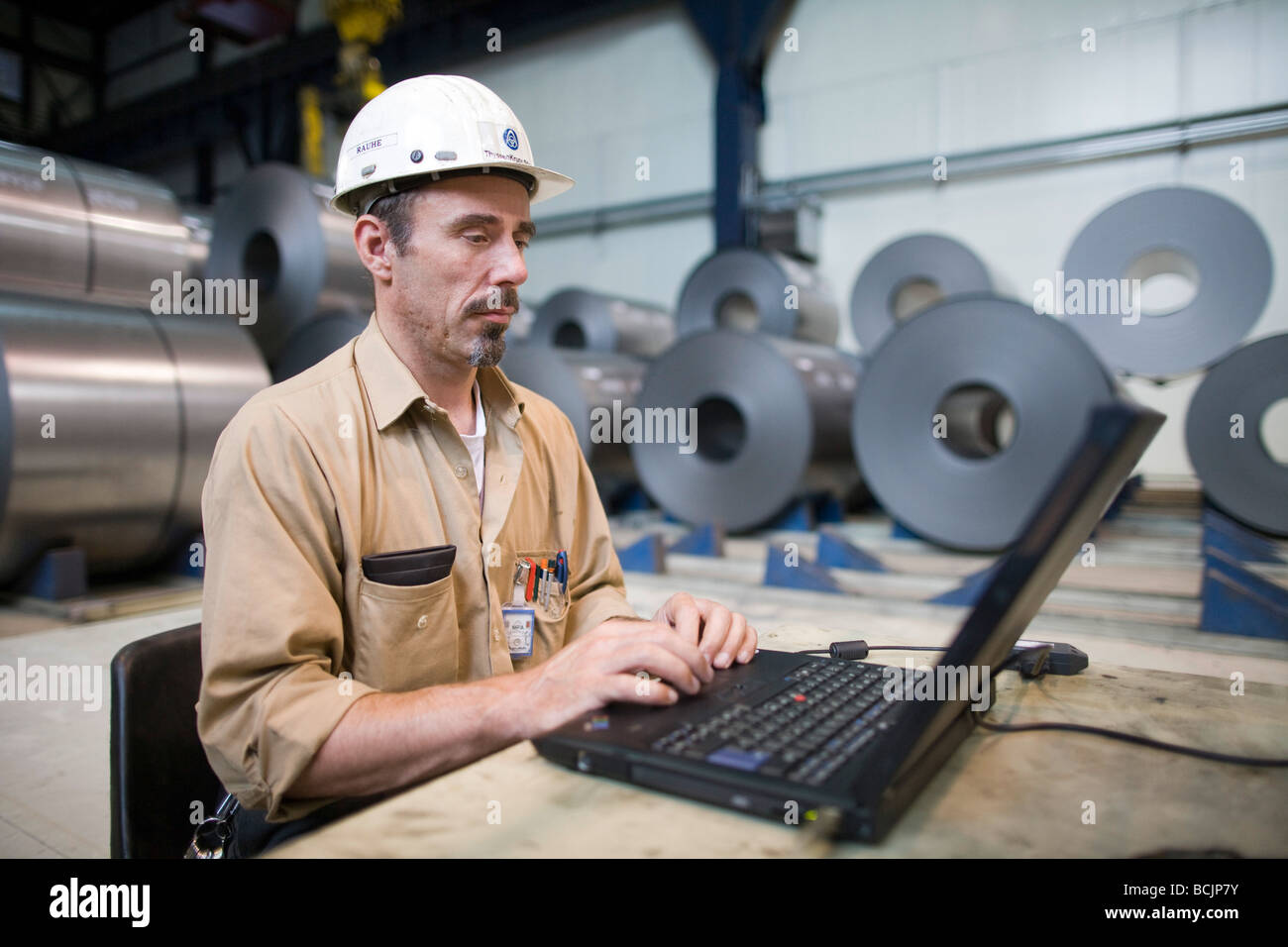 Worker at steel coil bracket - Stock Image