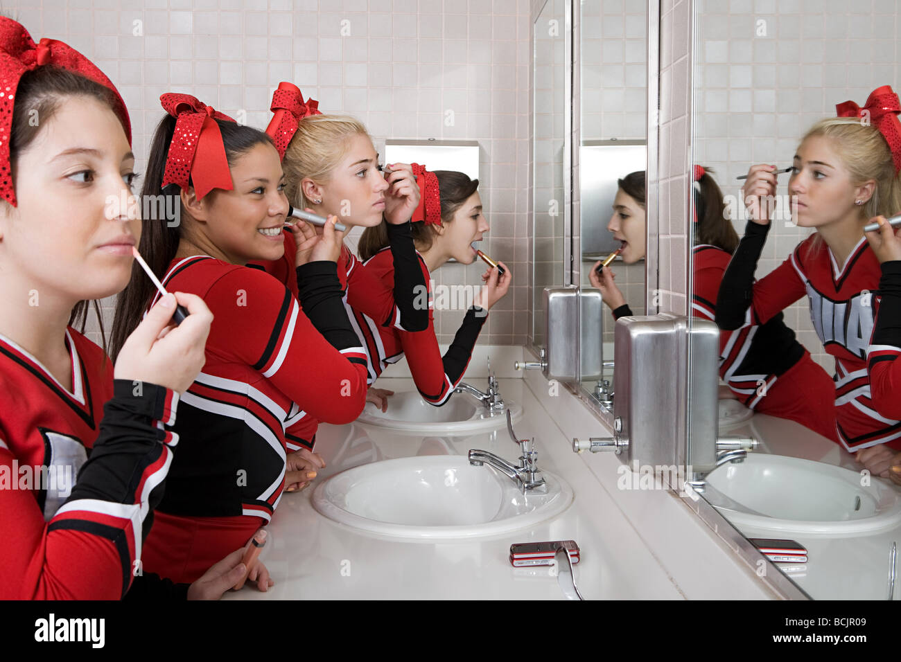 Cheerleaders putting on make up - Stock Image
