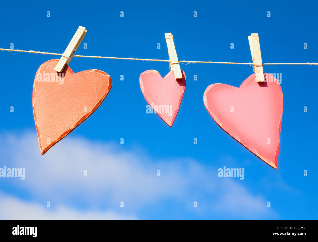 Three hearts on a washing line - Stock Image