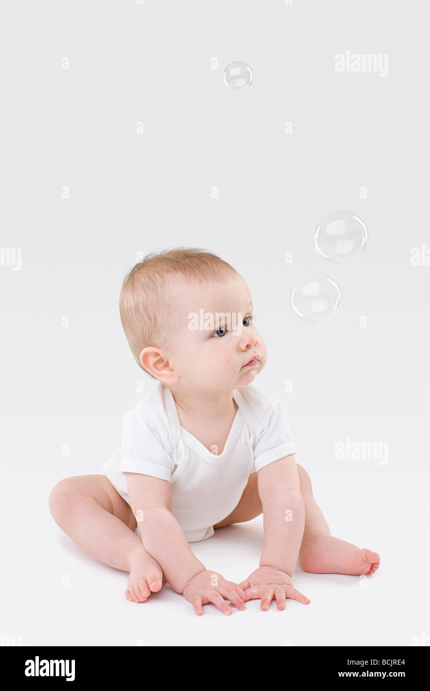 Baby looking at bubbles - Stock Image