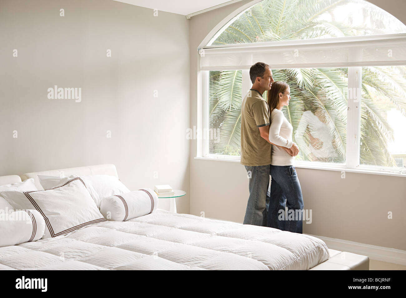 Couple looking out of bedroom window - Stock Image