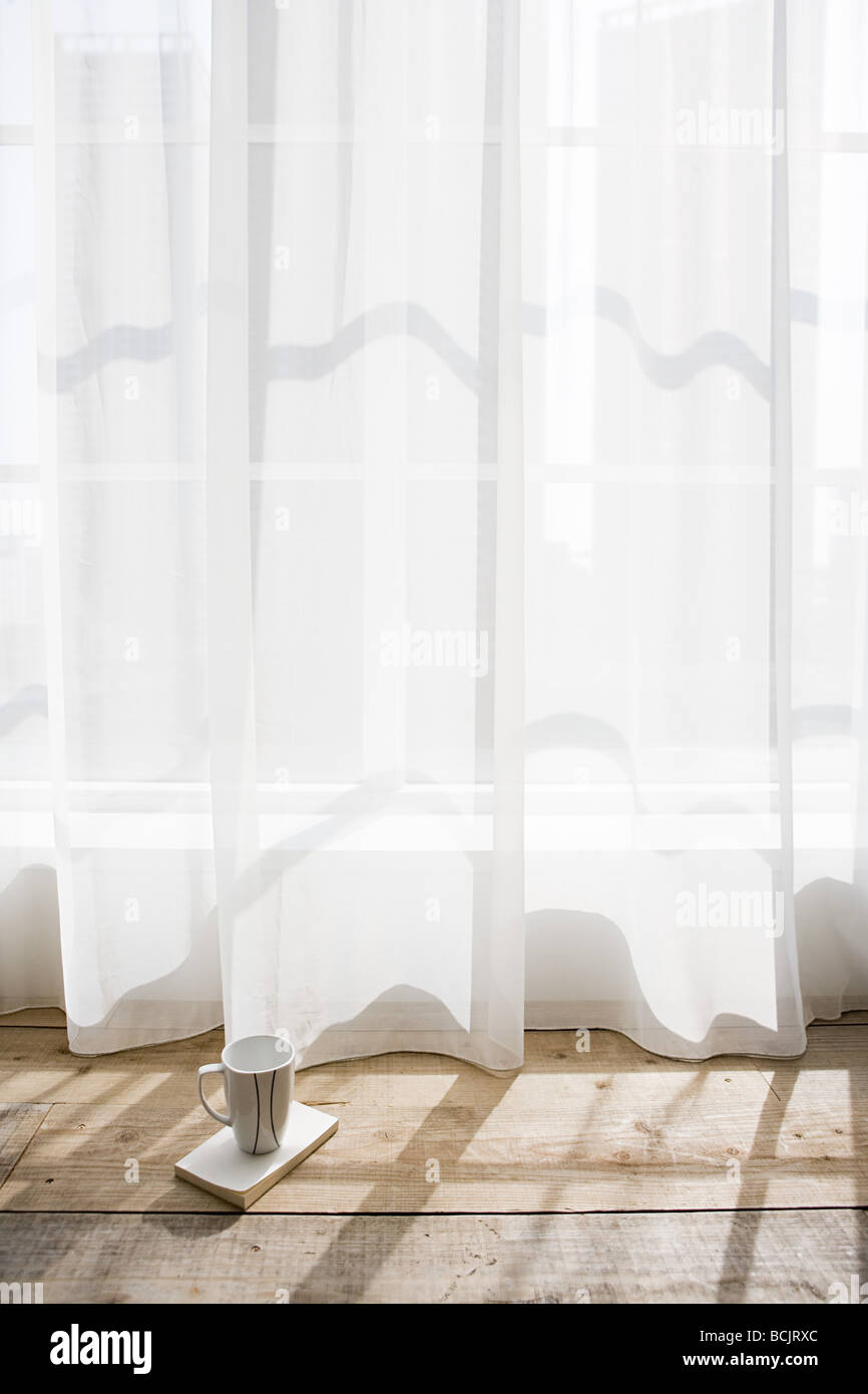 Coffee cup by net curtains - Stock Image