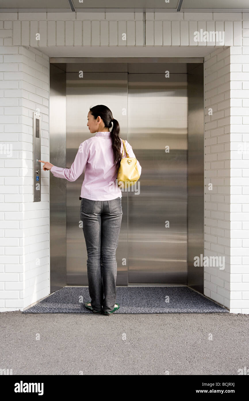 Japanese woman waiting for an elevator - Stock Image