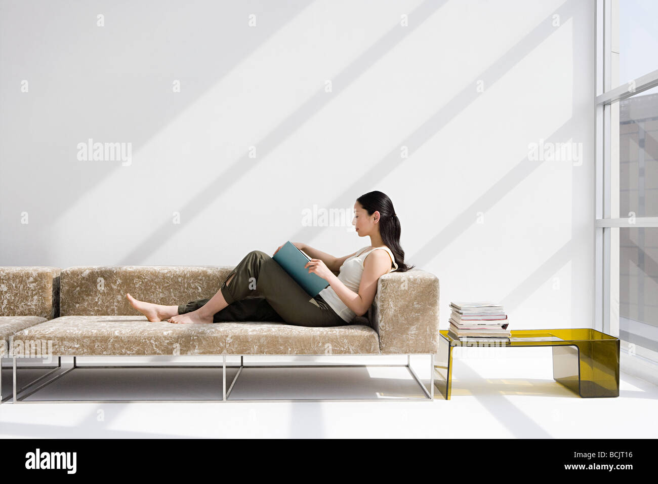 Woman reading on a sofa - Stock Image