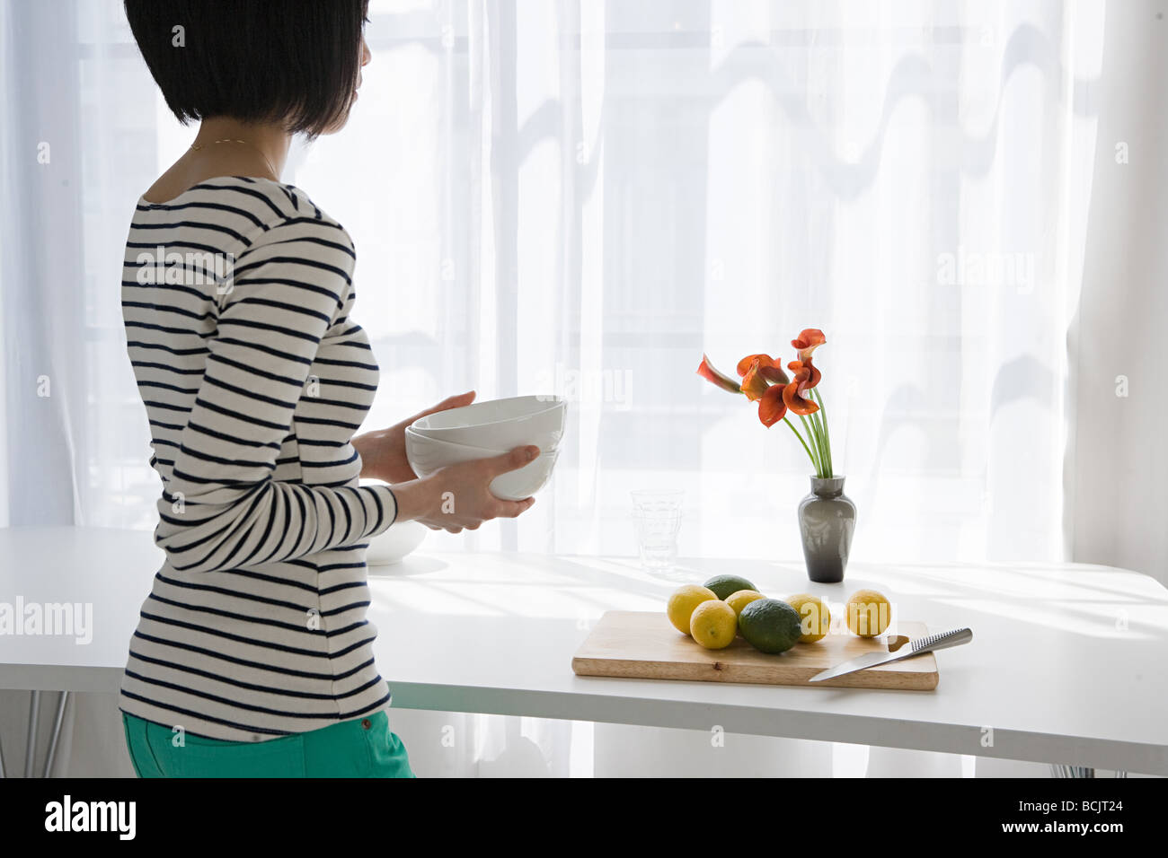 Japanese woman standing at window - Stock Image
