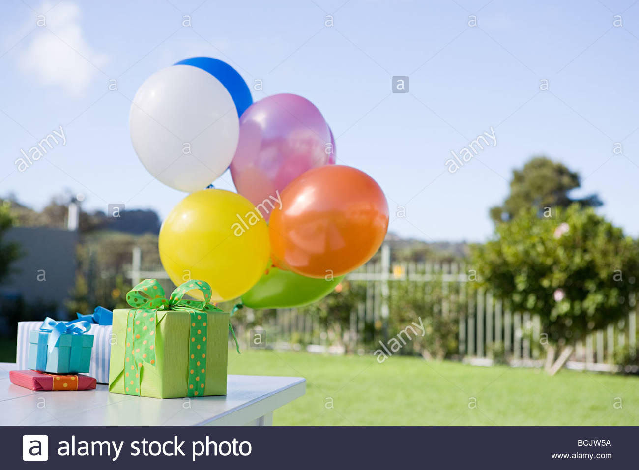 Balloons and birthday presents on table in garden - Stock Image