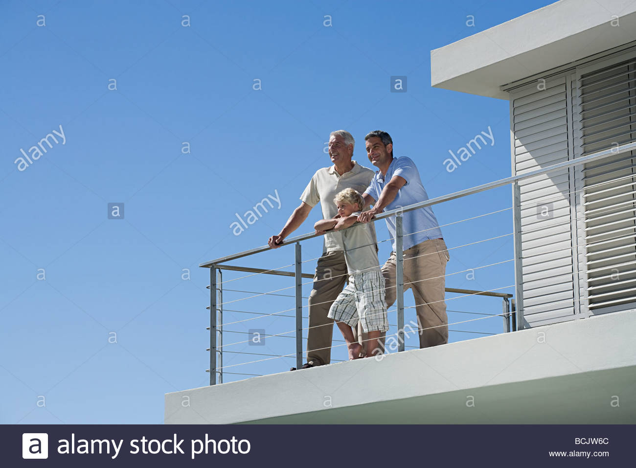 Senior man with his son and grandson looking at view from balcony - Stock Image
