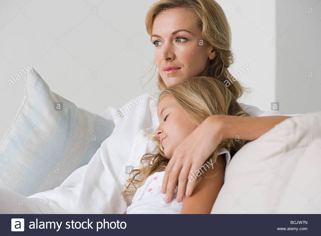 Woman relaxing on couch with arm around young daughter Stock Photo