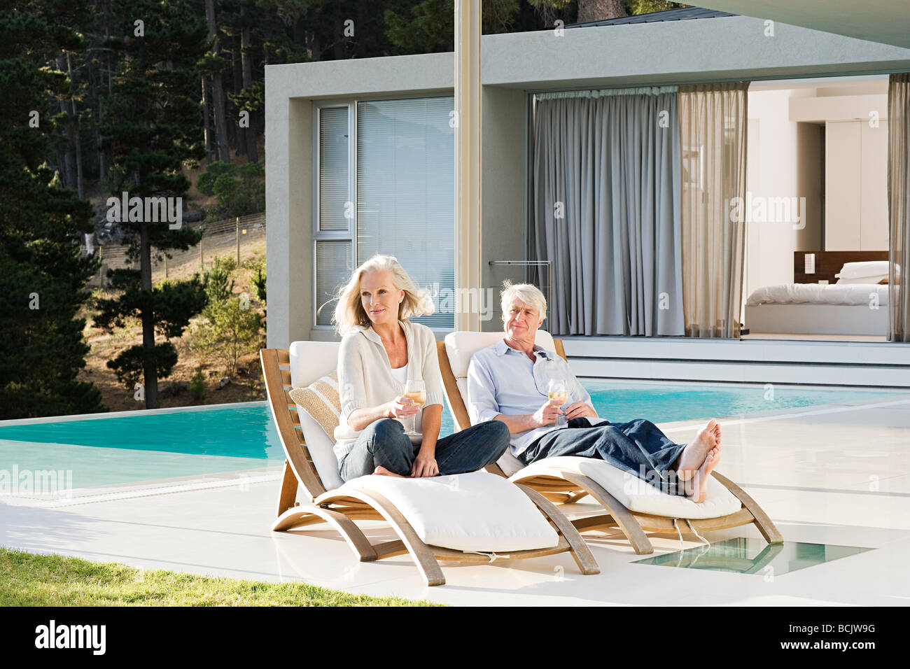 Middle aged couple relaxing on deck chairs by the pool Stock Photo