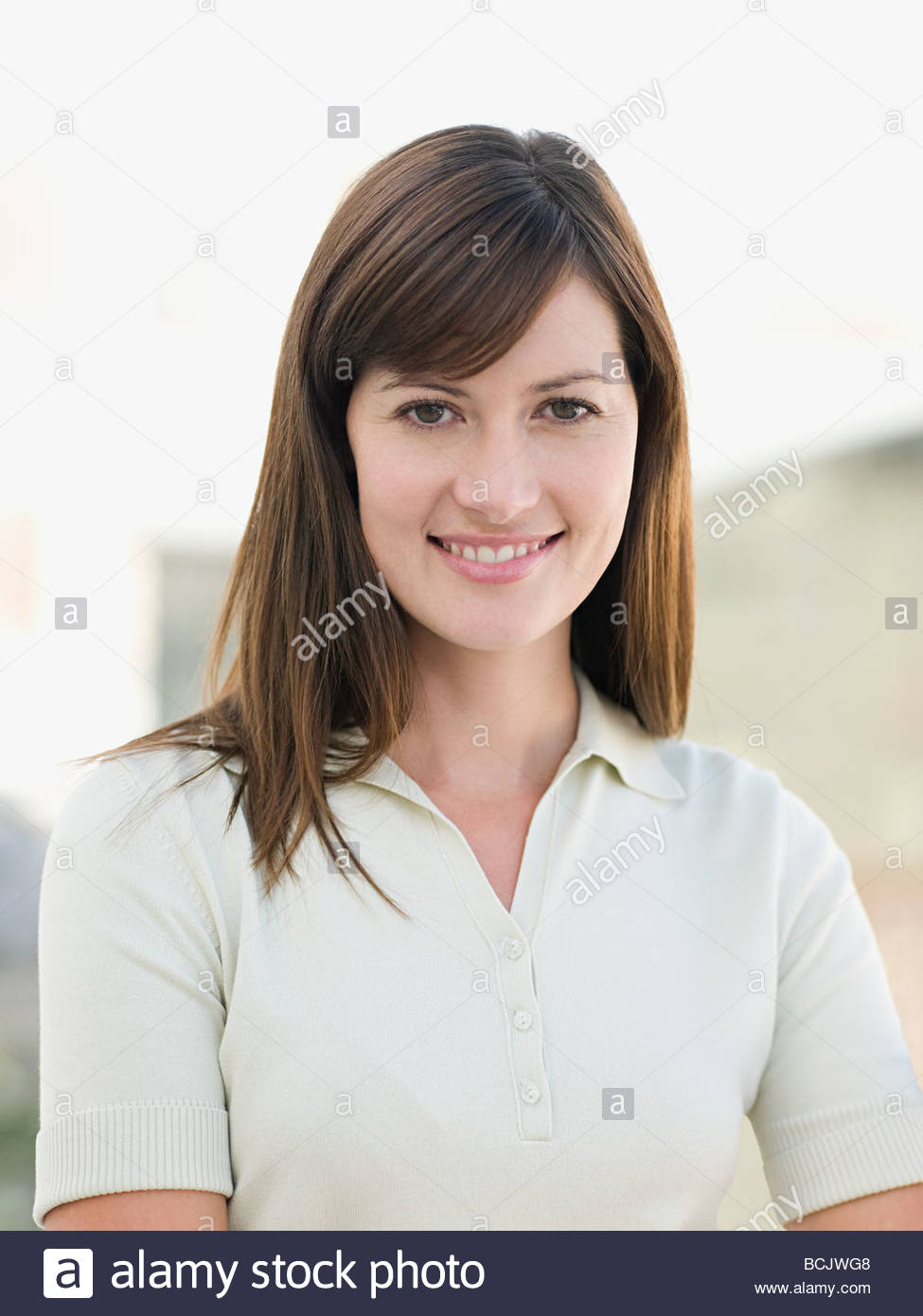 Portrait of smiling young woman standing outside - Stock Image