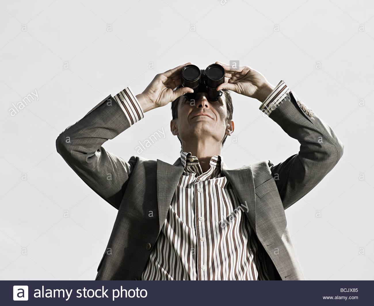 Man using binoculars - Stock Image