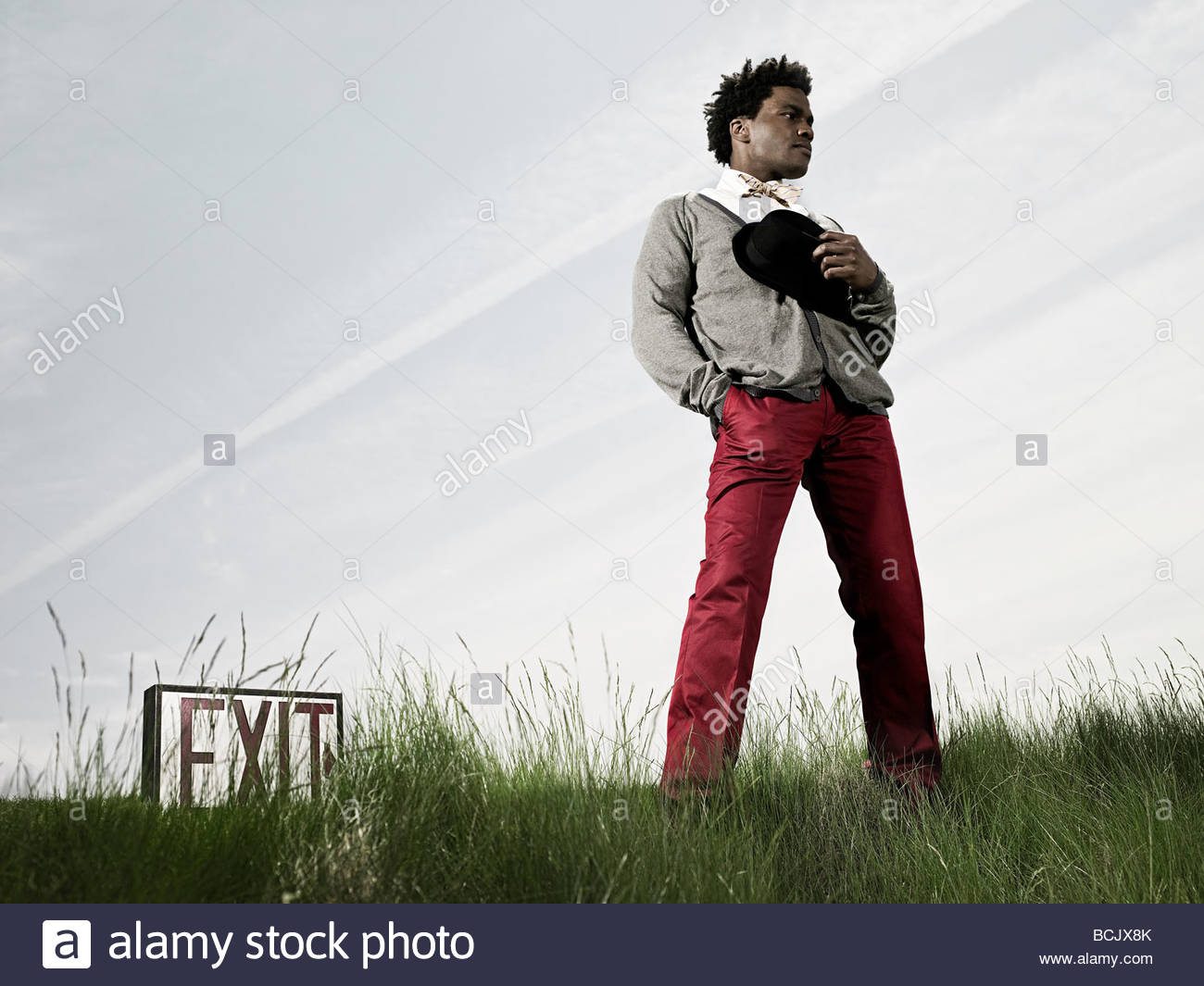 Man in field with exit sign - Stock Image