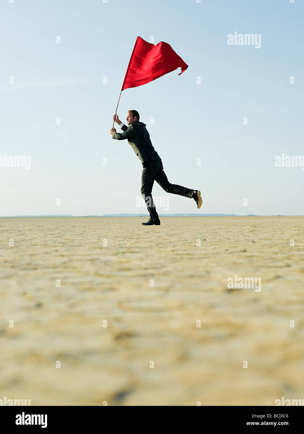 Businessman waving a red flag - Stock Image