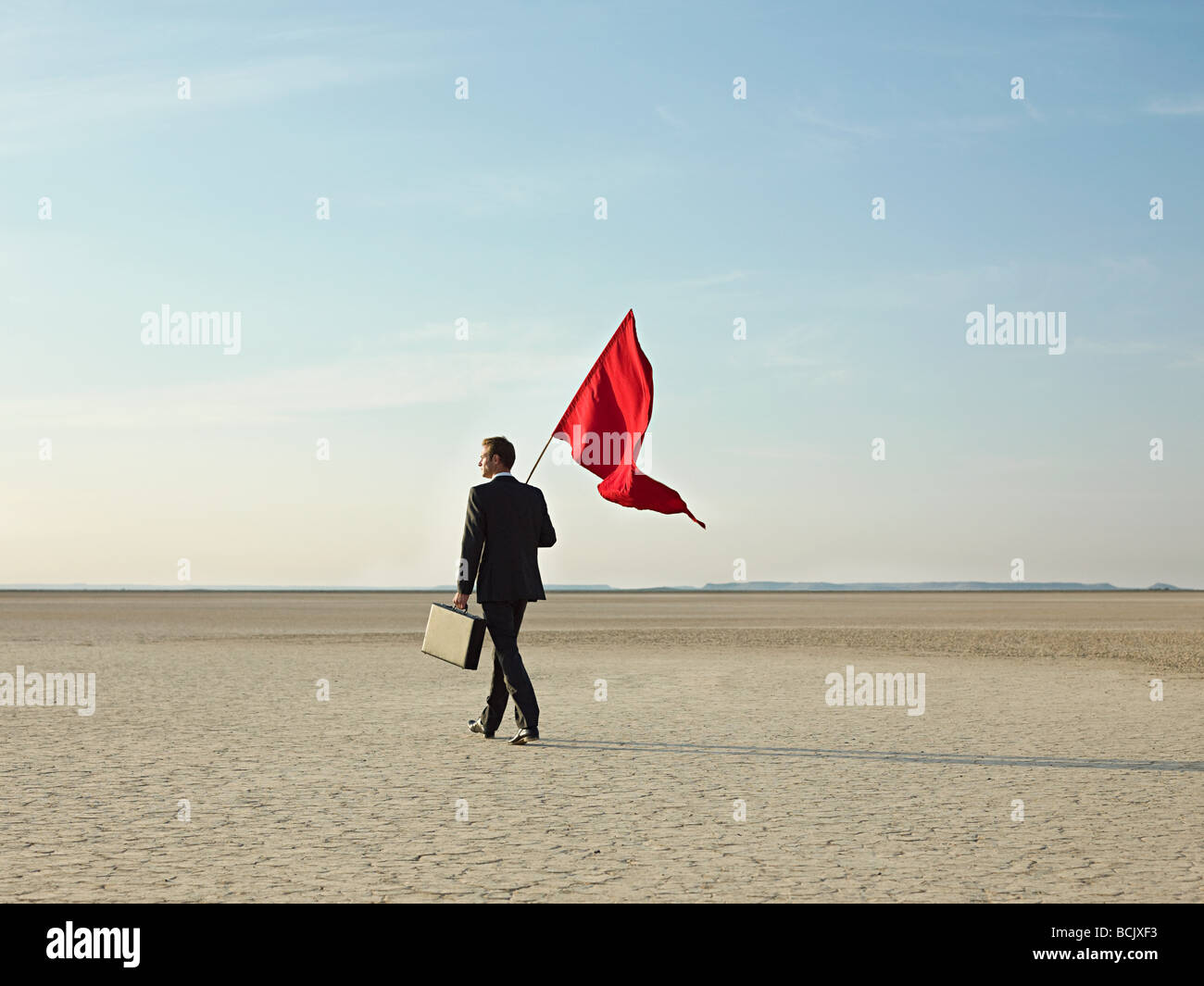 Businessman holding a red flag - Stock Image