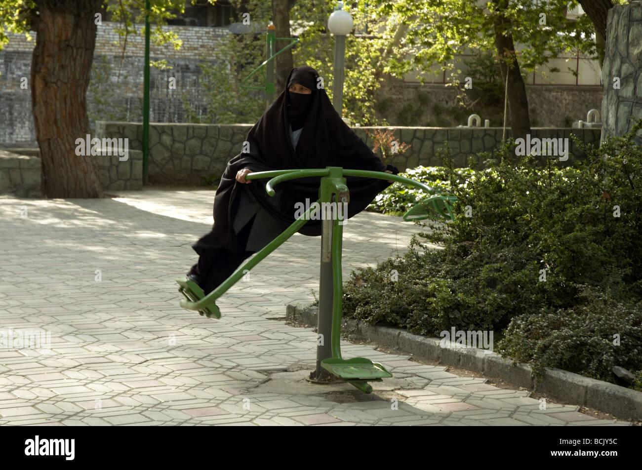 Woman in Burqa on an exercise machine in Tehran - Stock Image