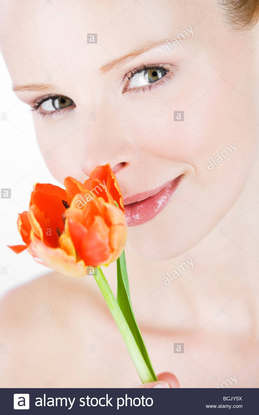 A portrait of a young woman smelling an orange tulip, close-up Stock Photo