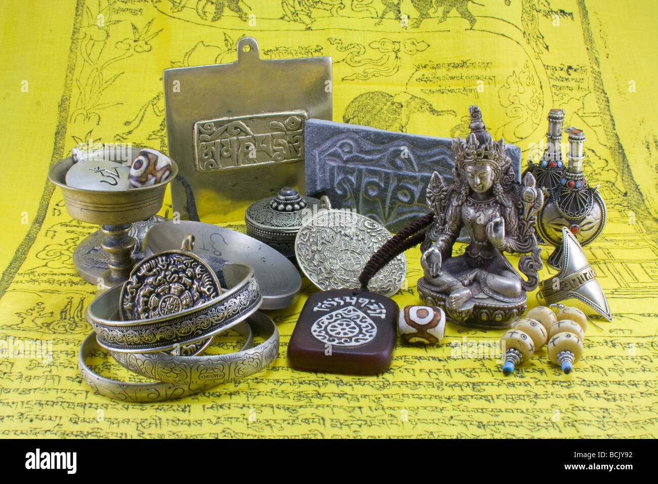 Various Tibetan artifacts and coins on a yellow cloth with Tibetan writings. - Stock Image