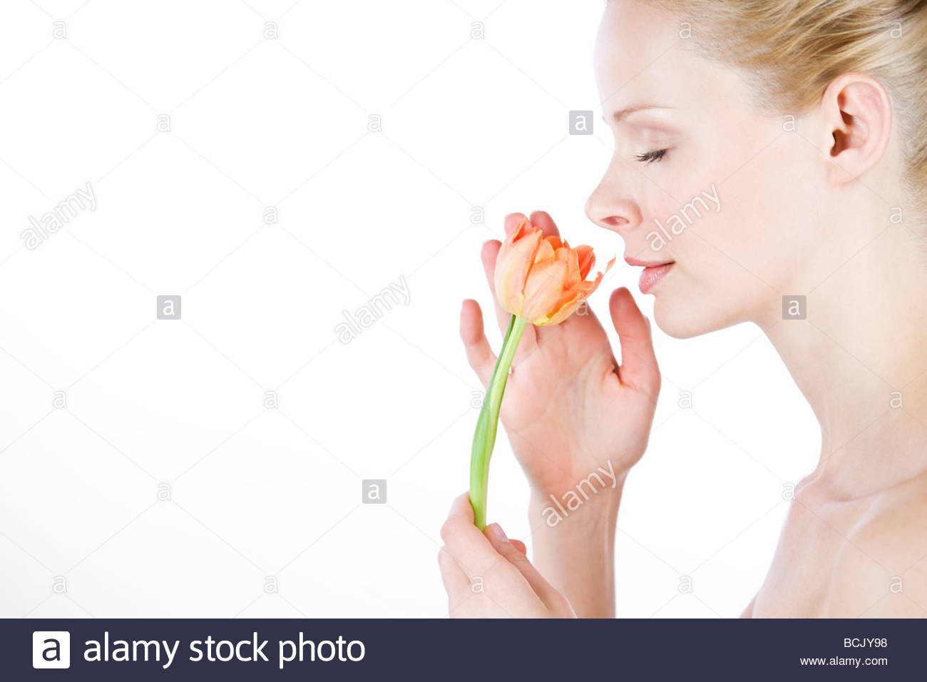 A young woman smelling an orange tulip, side view Stock Photo