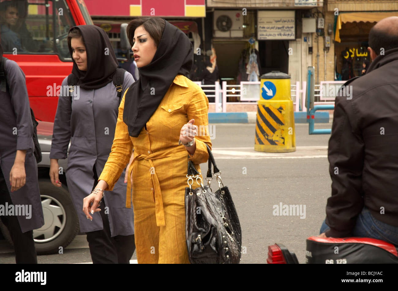 Young girl with makeup and compulsory hijab crossing the street in Tajrish, north of Tehran - Stock Image