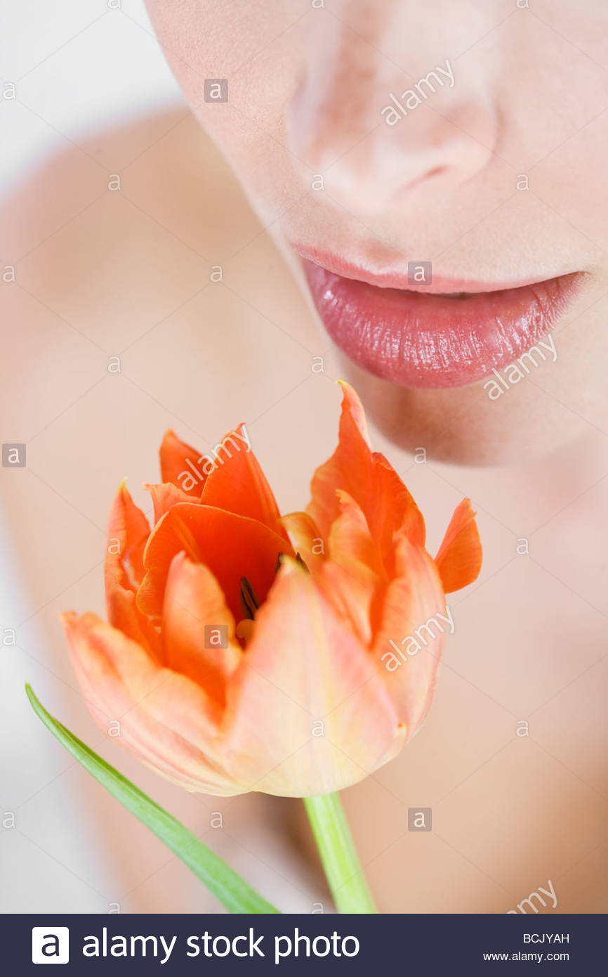 A young woman holding an orange tulip, close-up Stock Photo