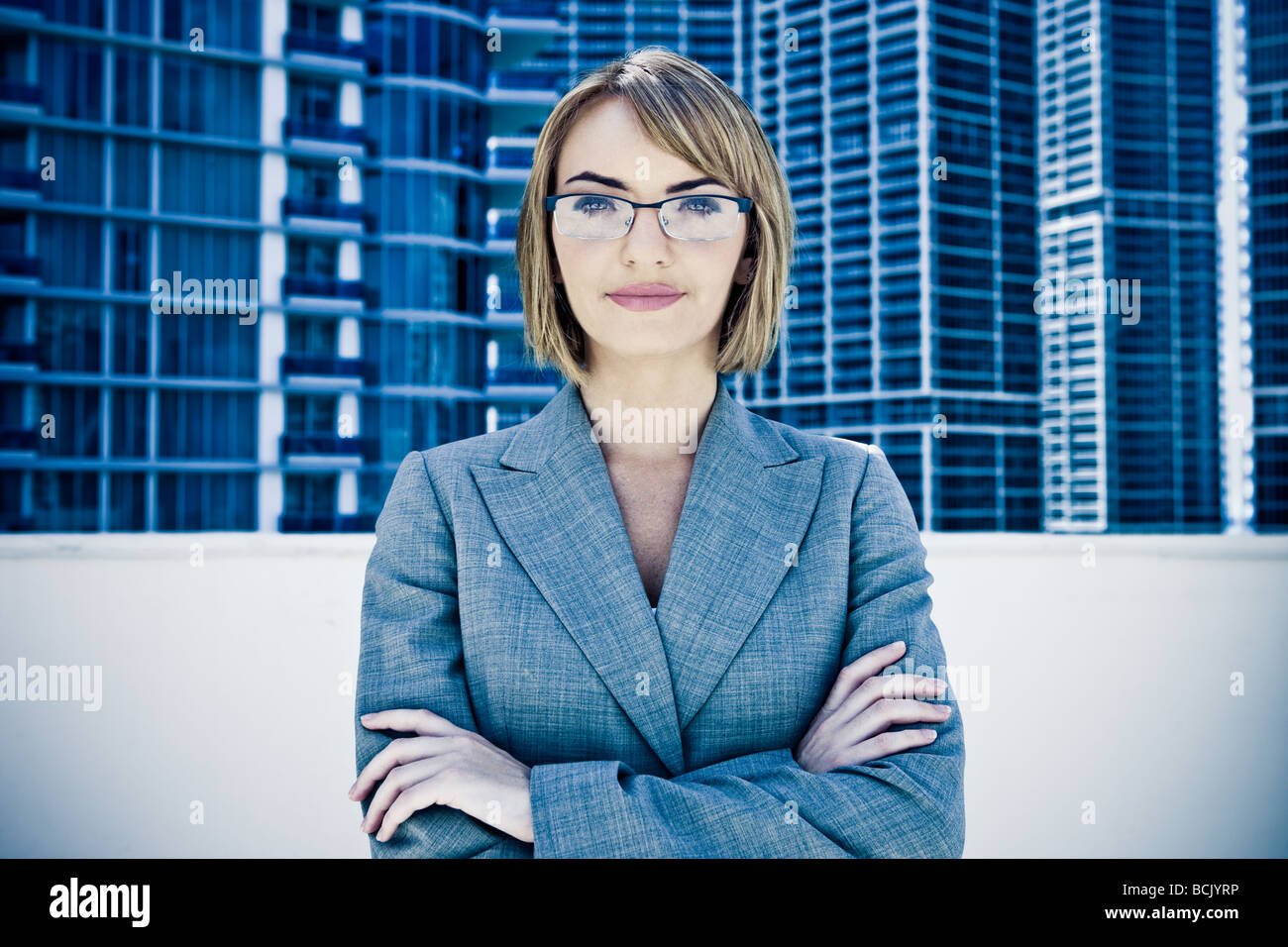 Young pretty businesswoman staring into camera - Stock Image