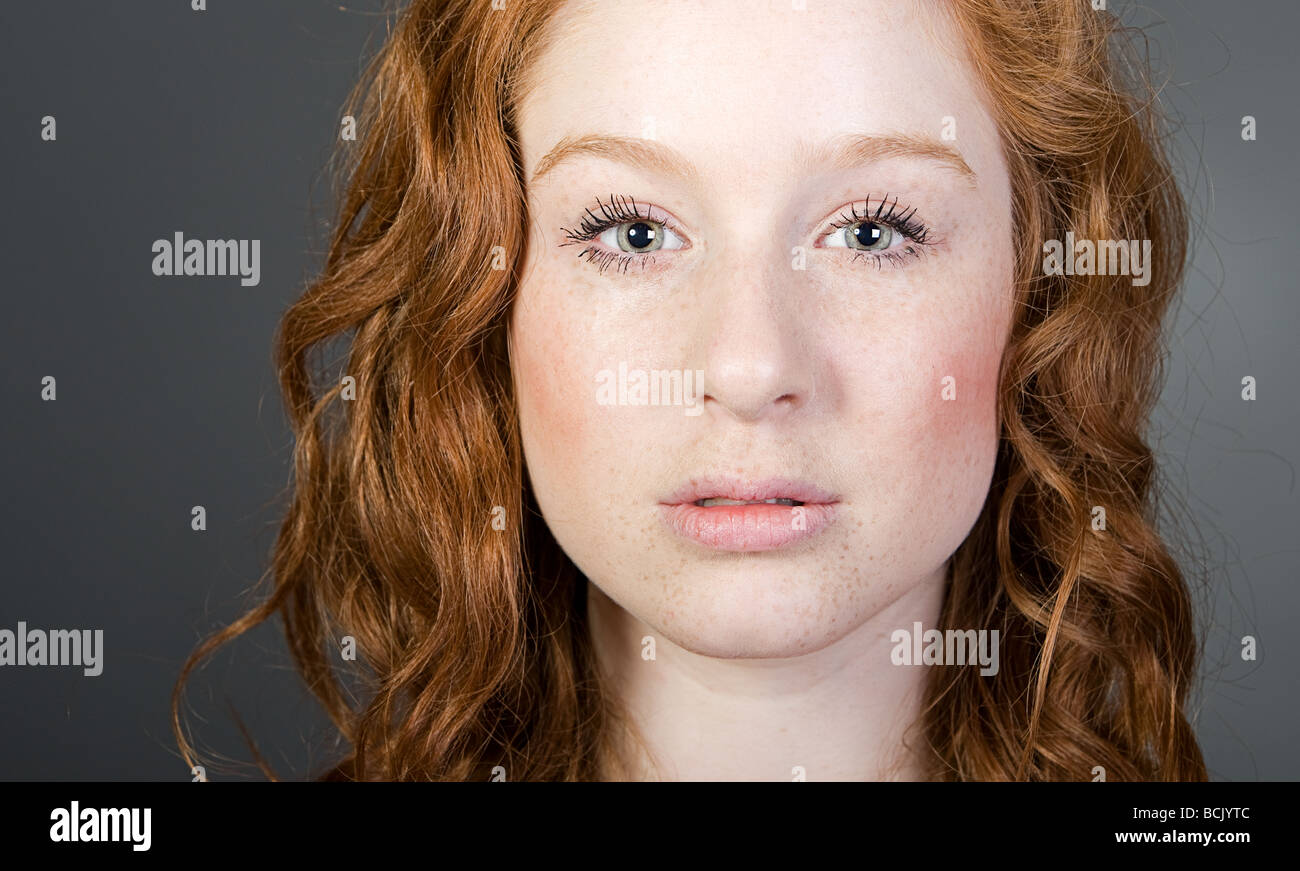 Studio Shot of a Stunning Red Headed Teenager against Grey - Stock Image