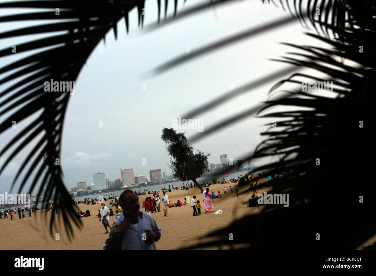 A colorful evening crowd at Chowpatty Beach with Nariman Point visible in the background in Mumbai (Bombay) in India - Stock Image