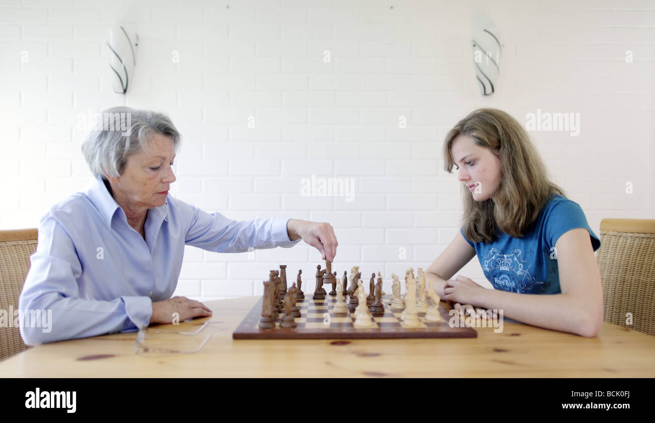 Elderly person gaming chess with her granddaughter - Stock Image