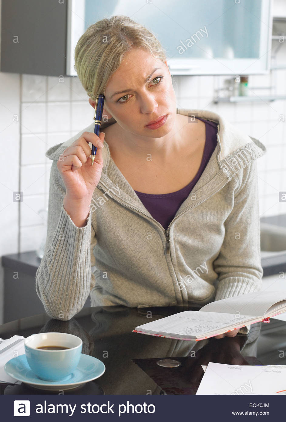 young woman checking her household costs - Stock Image