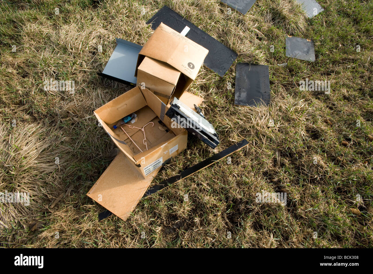 Trash dumped outside in the grass - Stock Image