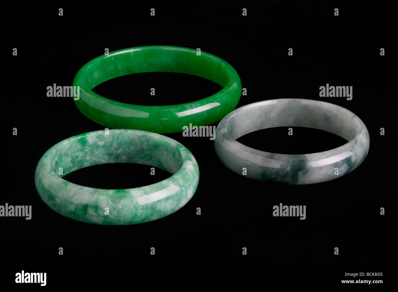Oriental Jade 'Jadeite' assorted bangles on black background - Stock Image
