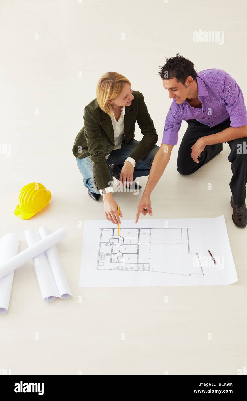 two architects looking at blueprint and smiling. High angle view - Stock Image