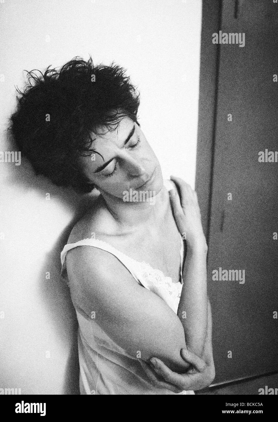 Woman leaning against wall with arm across chest, b&w - Stock Image