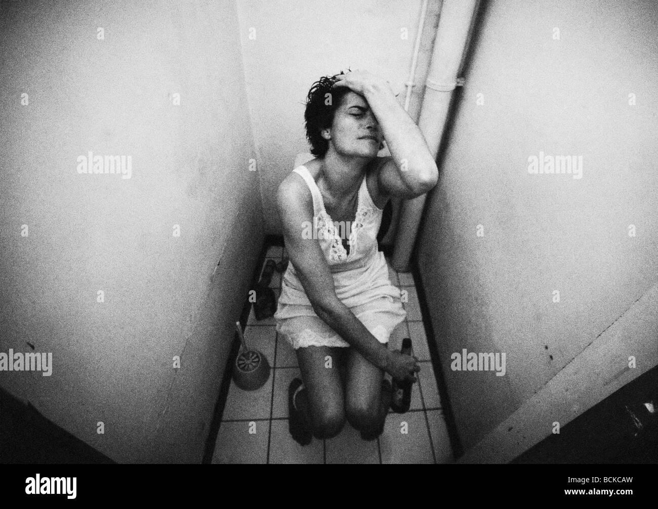 Woman sitting on toilet holding bottle, b&w - Stock Image