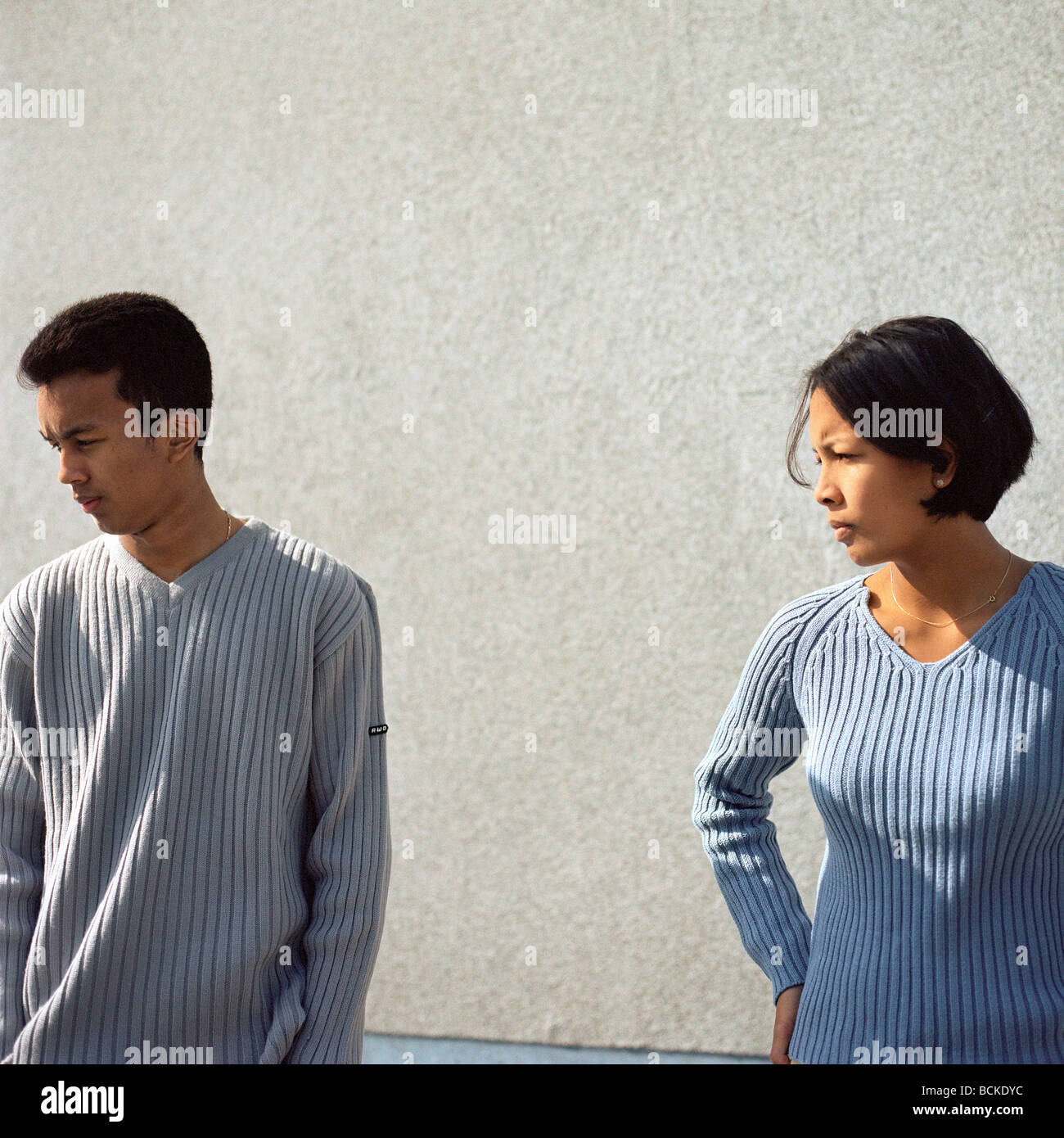 Couple standing apart in front of wall - Stock Image