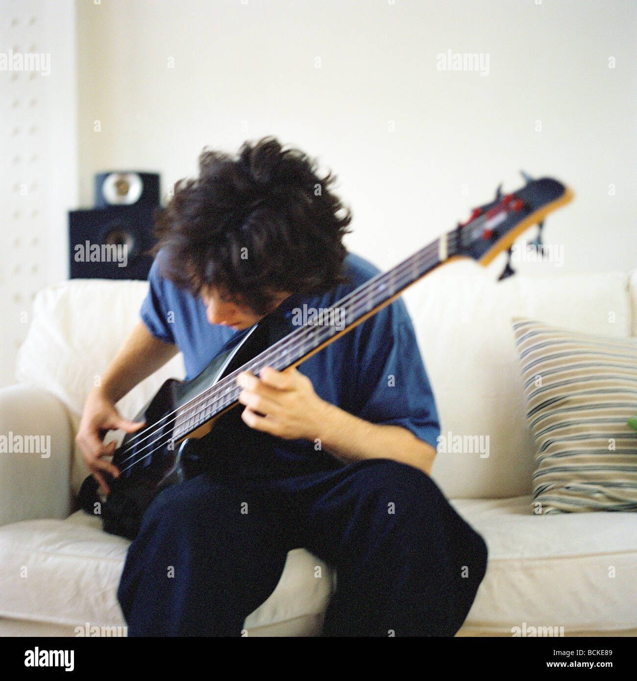 Young man sitting on sofa playing guitar - Stock Image