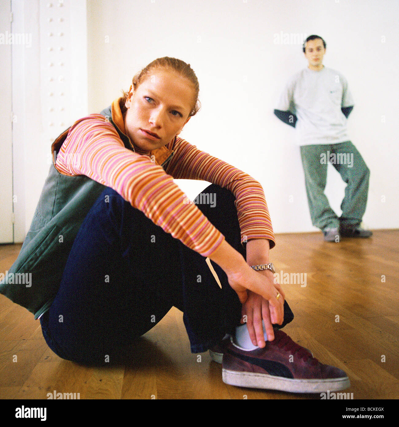 Young woman sitting on floor, young man leaning against wall - Stock Image