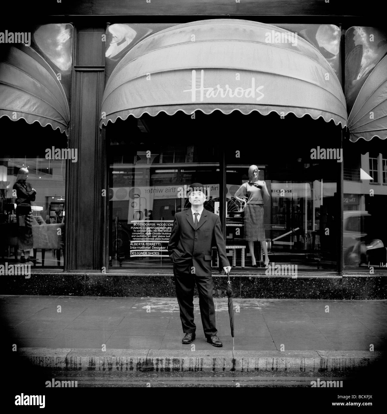Traditional British city gentleman with bowler hat and umbrella outside Harrods department store, London - Stock Image