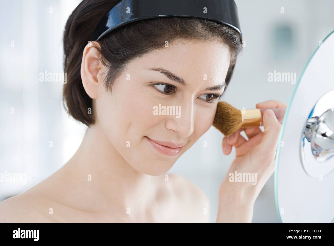 Young woman applying make up Stock Photo