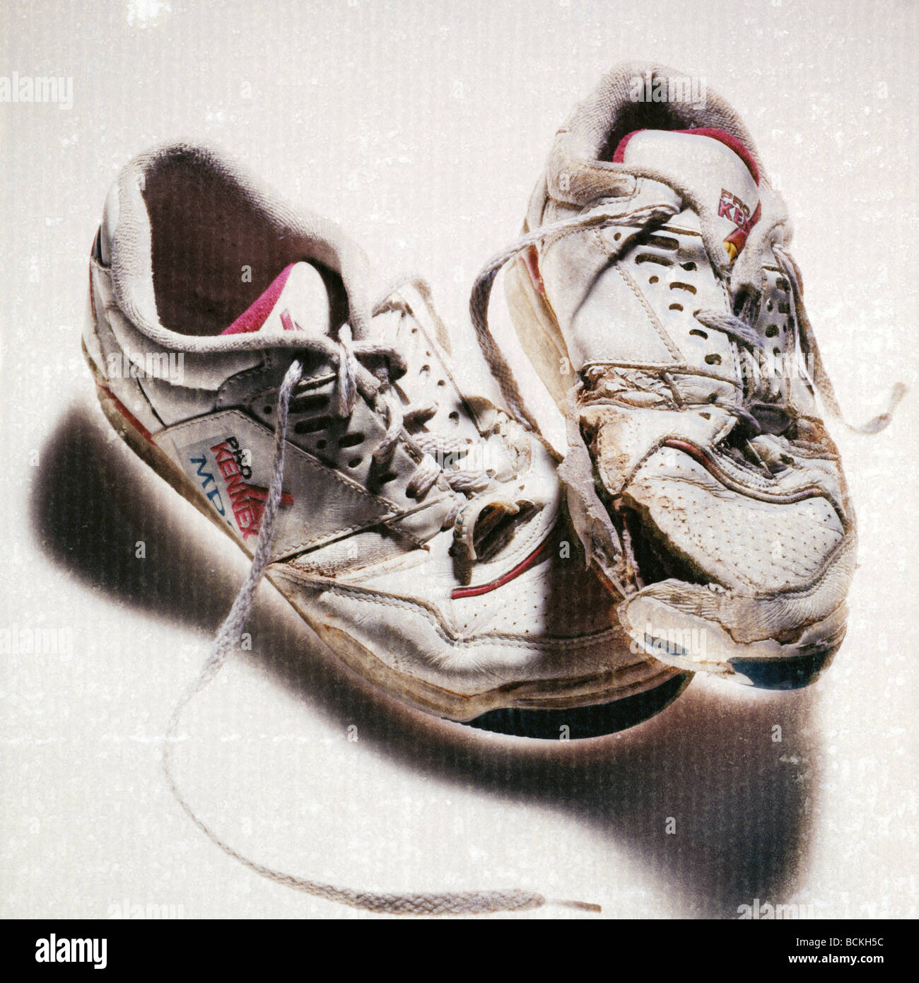 Worn out tennis shoes - Stock Image