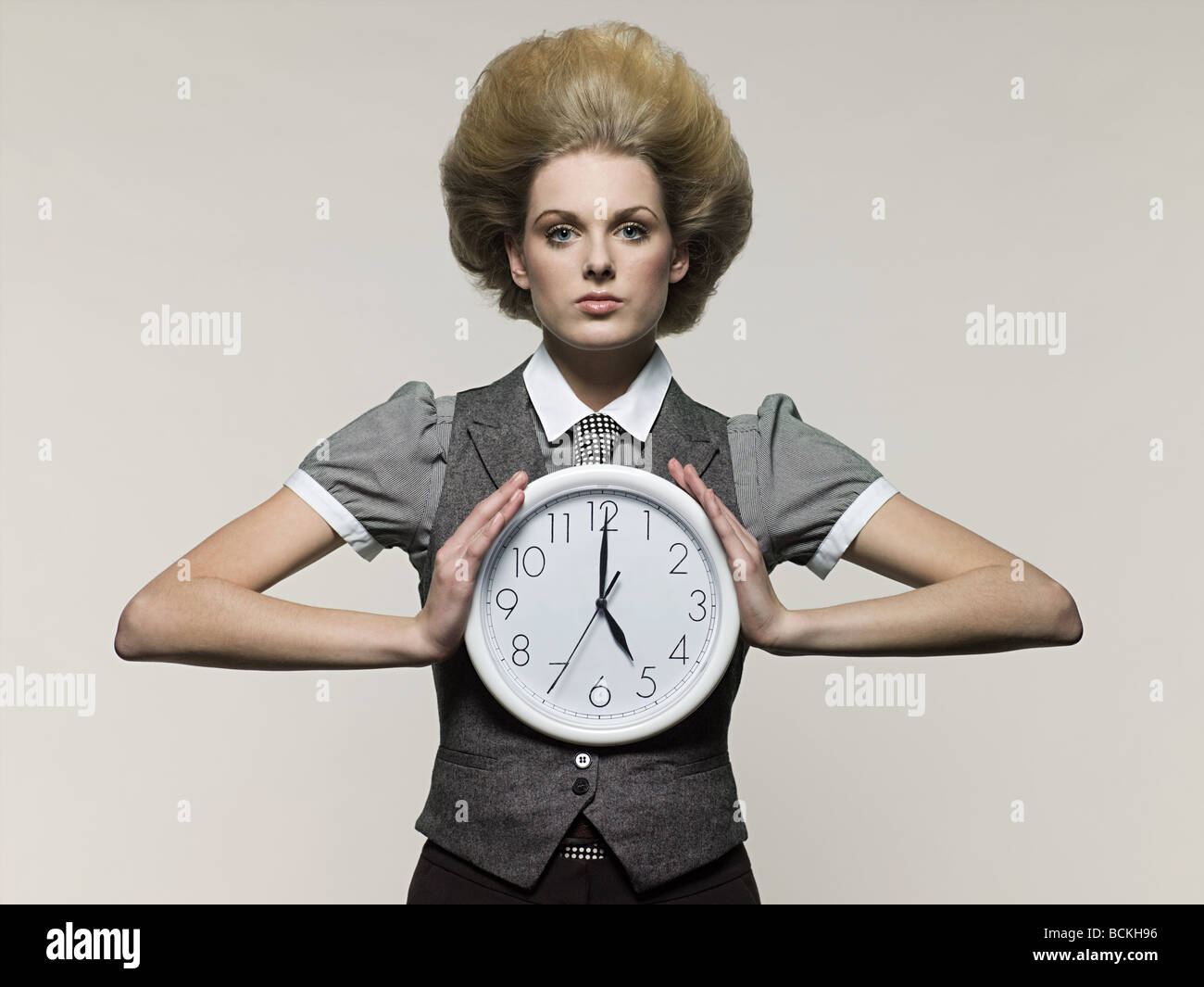 Businesswoman holding clock - Stock Image